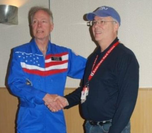Dr. Olsen, KC2ONX, in space overalls shakes hands with Gerry Jurrens, N2GJ