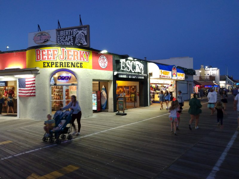 Scene of boardwalk with several shops lit up for the evening